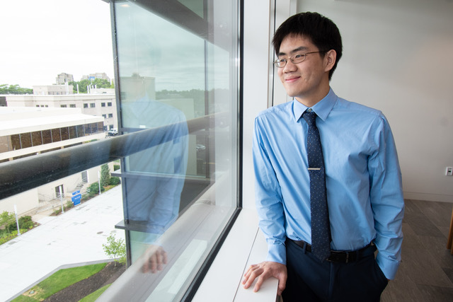 Image of young entrepreneur Michael Lai standing near window and looking out of it